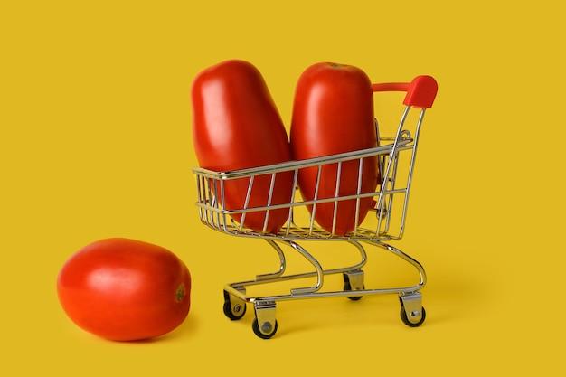 Mini cesta de la compra con tomates aislados sobre fondo amarillo. venta minorista. concepto de ventas.