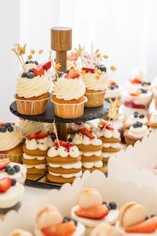 Mini cupcakes de chocolate cubiertos con mini rosquillas rosas en una mesa de postres