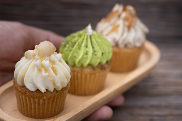 Mini cupcakes sabrosos en un fondo del vintage, postre dulce