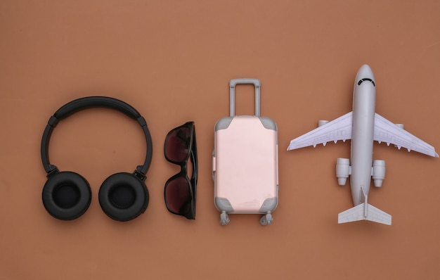 Mini equipaje de viaje con auriculares estéreo, gafas de sol y avión sobre fondo marrón. planificación de viajes. vista superior