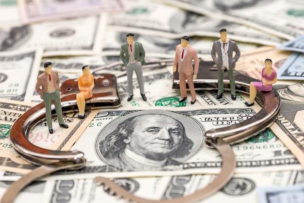 Mini figuras cerca de esposas de acero sobre fondo de billetes de dólar