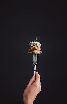 Mini hamburguesa negra en el tenedor
