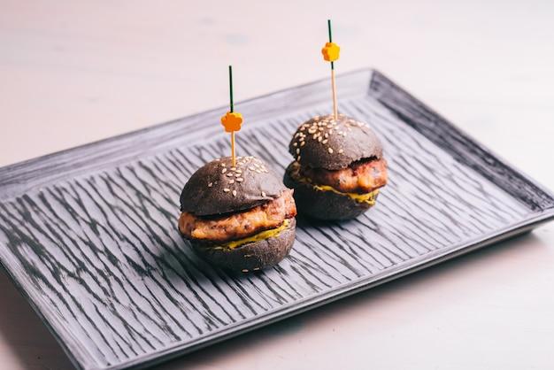 Mini hamburguesa de ternera gourmet con pan negro en un plato