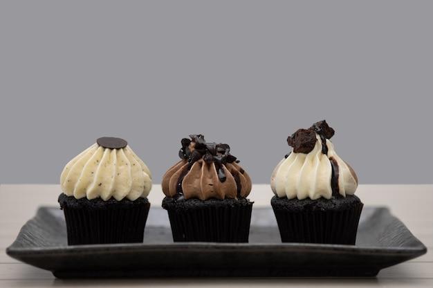 Mini magdalenas sabrosas del chocolate en un fondo del vintage, postre dulce