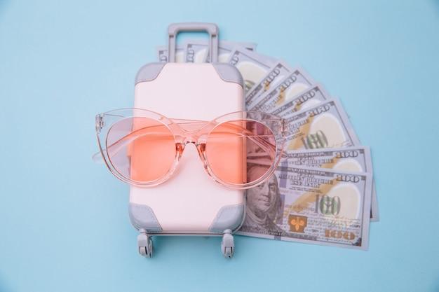 Mini maleta de equipaje de viaje, gafas de sol y billetes de dinero en superficie azul. ahorros por concepto de viaje