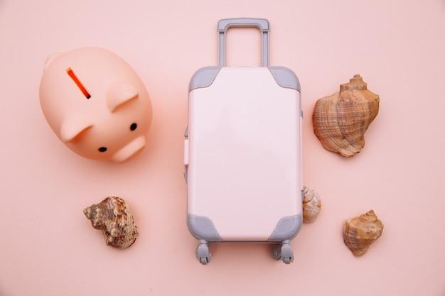 Mini maleta de equipaje de viaje y hucha en superficie rosa. ahorre dinero para viajar
