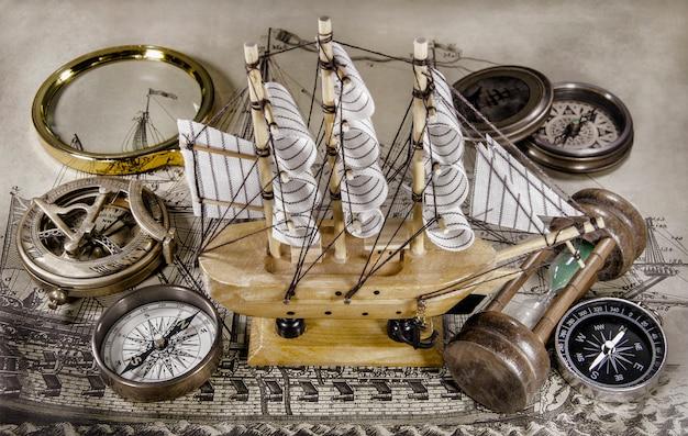 Mini modelo de barco con brújula y reloj de arena.