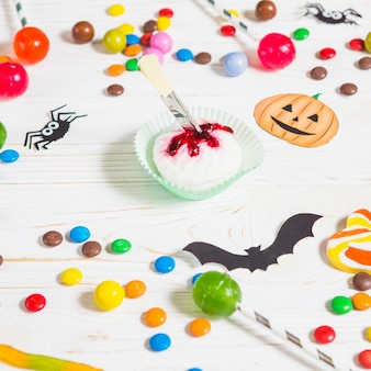 Mini muffin cerca de pequeños dulces, murciélagos, arañas y bombones