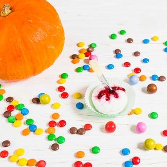 Mini muffin entre pequeños caramelos cerca de calabaza