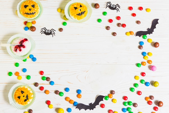Mini muffins cerca de pequeños caramelos, murciélagos y arañas
