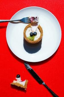 Mini pastel de queso decorado con arándanos sobre un fondo rojo.