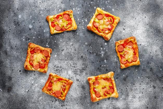 Mini pizzas de hojaldre con salchichas.