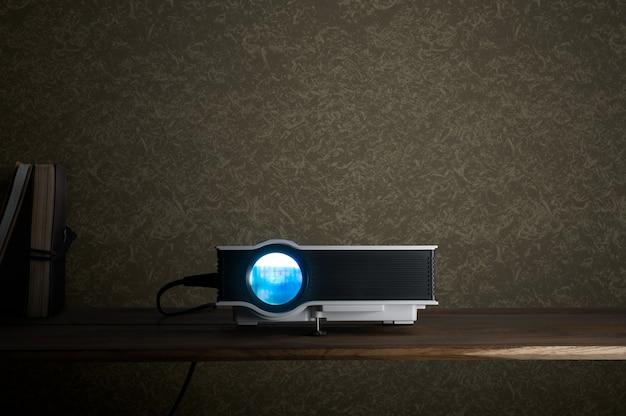 Mini proyector llevado en la tabla de madera en un concepto del teatro casero del proyector del sitio.