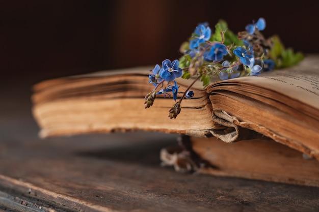 Mini ramo de flores silvestres en un cubo decorativo en libros antiguos en la ventana del pueblo.