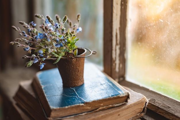 Mini ramo de flores silvestres en un cubo decorativo en libros antiguos