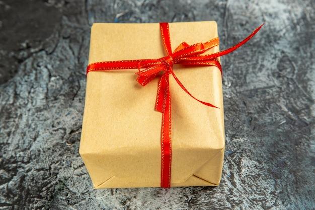 Mini regalo de vista inferior atado con cinta roja sobre fondo oscuro aislado