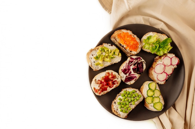 Mini sandwich con baguette francés caviar tomate pepino rábano guisantes sobre un fondo blanco.