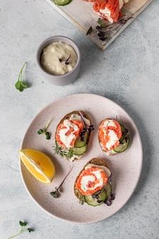 Mini sándwiches de salmón ahumado, queso crema, pepino y microgreen sobre pan de centeno.