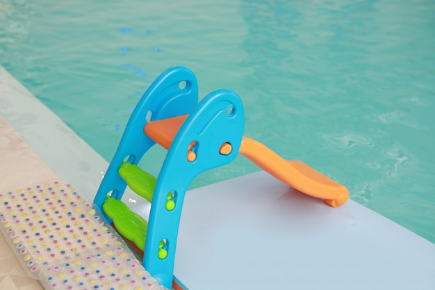 Mini slider para niños junto a la piscina.