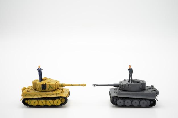 Miniatura 2 personas empresarios de pie en el tanque de juguete. negociando en los negocios.