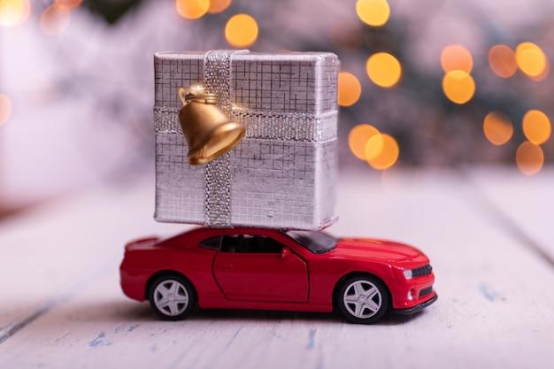 Miniatura coche rojo con una gran caja plateada
