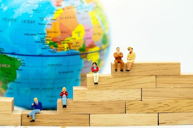 Miniatura de empresarios sentados en caja de madera con el mundo