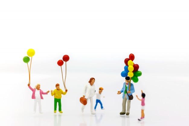 Miniatura gente niños sosteniendo globo con luz solar