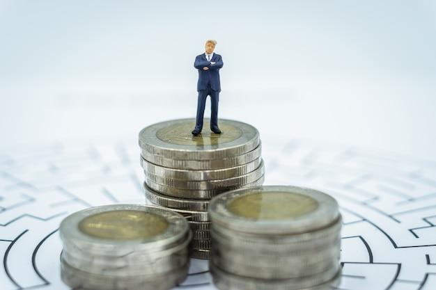 Miniatura de hombre de negocios de pie en la pila