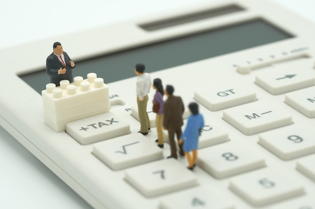 Miniatura de personas paga en cola ingresos anuales (impuestos) del año en la calculadora.