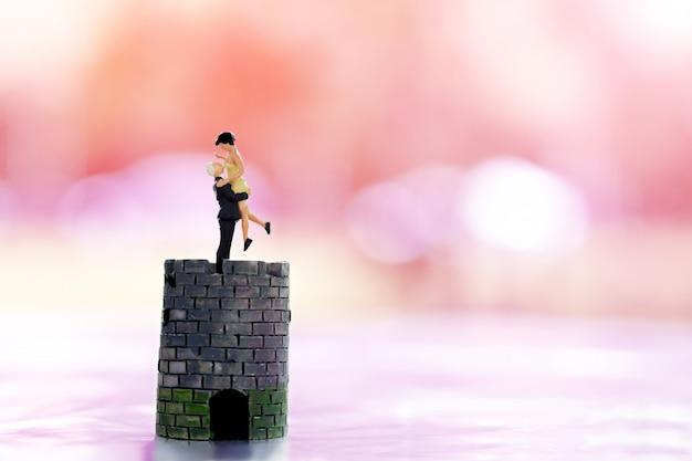 Miniatura personas pareja amante de pie en el castillo y la pequeña casa con fondo rosa.
