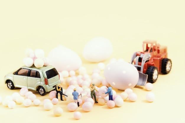 Miniatura de personas preparando vacaciones de pascua. composición de enfoque selectivo y tonos de color pastel suave