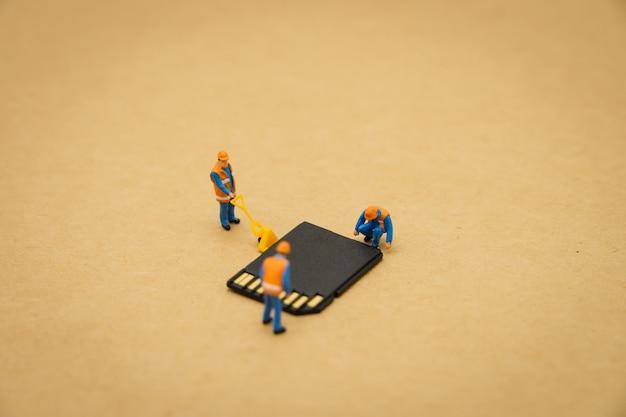 Miniatura de personas reparación de trabajadores de construcción con tarjeta de almacenamiento o tarjeta de memoria