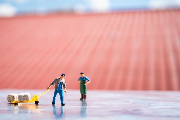 Miniatura de personas, trabajadores y empleadores en el sitio de trabajo, utilizando para el concepto de logística y de negocios
