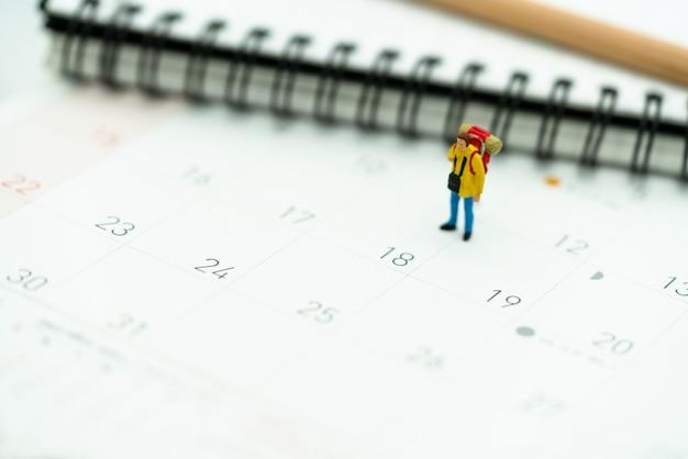 Miniatura de turistas con mochilas de pie en el calendario de viaje