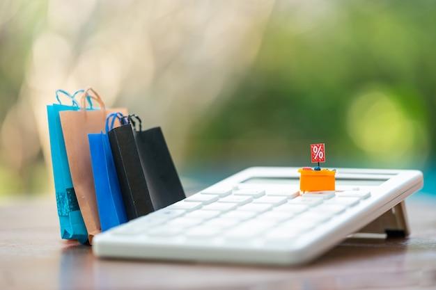 Miniaturas, compradores y estantes de exhibición a la venta en la calculadora y bolsas de compras como telón de fondo.