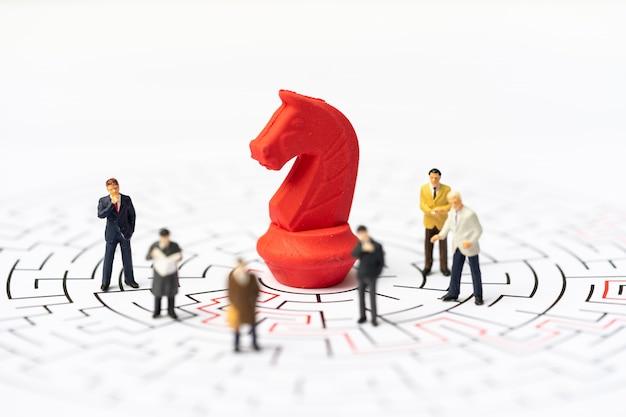 Miniaturas, hombres de negocios y piezas de ajedrez en el laberinto o laberinto que descifran la salida.