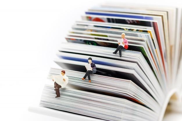 Miniaturas personas leyendo con libro, educación o concepto de negocio