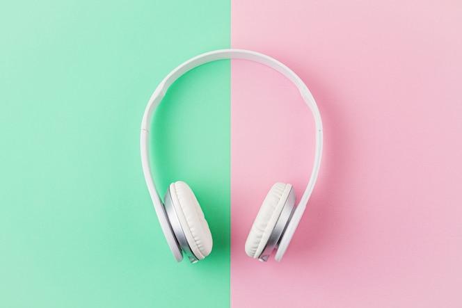 Minimal flat lay con auriculares inalámbricos sobre fondo rosa y menta claro.