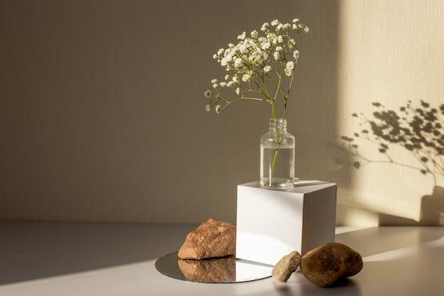 Minimalismo bodegón con una rama de una flor de gypsophila de pie sobre un cubo de papel blanco y piedras