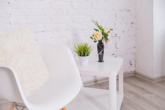 Minimalista interior de la casa blanca con silla, mesa de café con plantas tropicales en florero. copie el espacio para la inscripción, simule el cartel. pared de ladrillo vacía parquet de madera marrón estilo escandinavo.