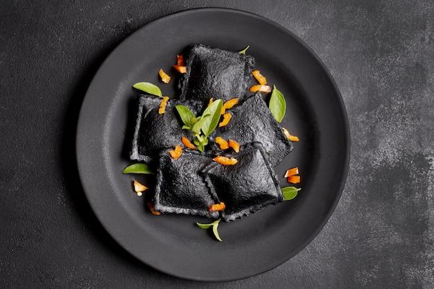Minimalista plana pone ravioles negros en plato