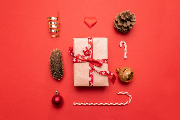 Mínimo año nuevo de regalo, decoraciones doradas de navidad, conos de pino en rojo. vista plana, vista superior