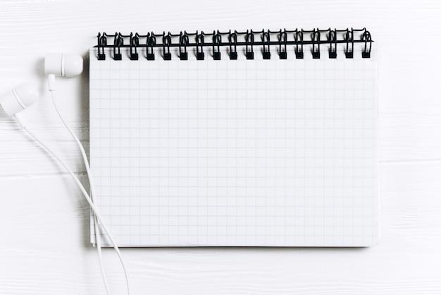 Mínimo espacio de trabajo - foto plana de creación plana de escritorio de espacio de trabajo con cuaderno de bocetos y auriculares blancos en el espacio de copia de fondo blanco. vista superior, fotografía plana.