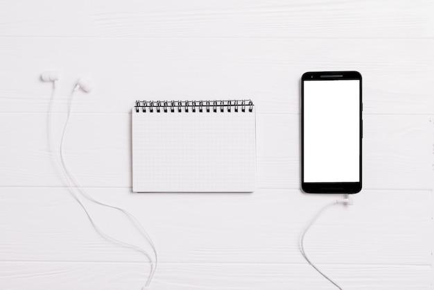 Mínimo espacio de trabajo - foto plana creativa de escritorio de espacio de trabajo con cuaderno de bocetos y teléfono móvil con pantalla en blanco sobre fondo blanco. vista superior, fotografía plana.