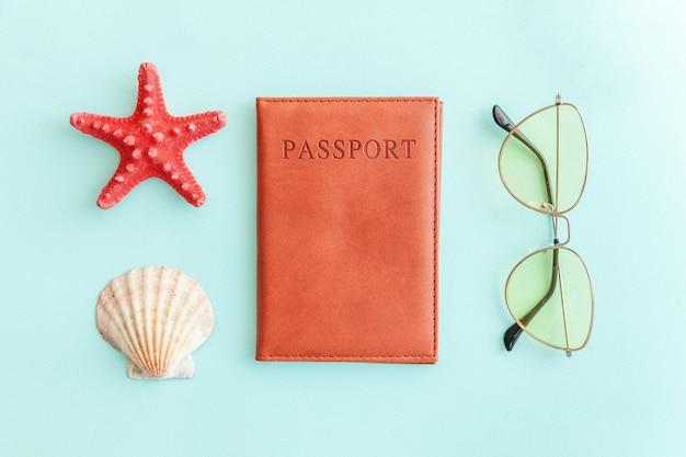 Mínimo plano simple con gafas de sol tipo pasaporte y carcasa en azul pastel, colorido, moderno, turístico.