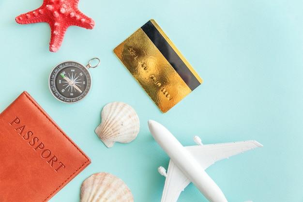 Mínimo plano simple con pasaporte de avión, brújula, tarjeta de crédito dorada y concha en azul pastel. esenciales turísticos