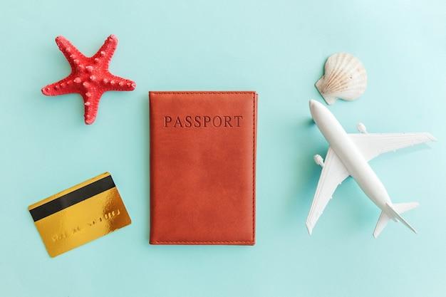 Mínimo plano simple con pasaporte de avión, tarjeta de crédito dorada y concha en azul pastel