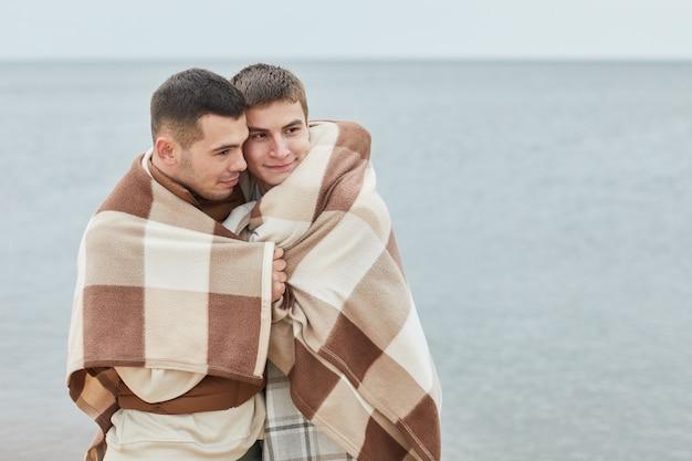 Mínimo retrato de joven pareja gay abrazada en la playa envuelto en una manta con agua en el fondo, espacio de copia