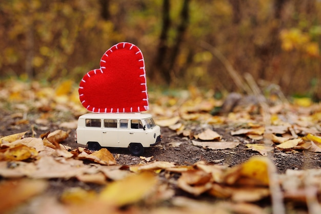 Minivan de coches de juguete afortunado en el techo de un gran corazón rojo
