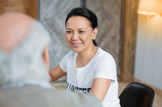 Minuto para la historia. atractivo voluntario alegre sonriendo mientras está sentado sobre un fondo borroso y escuchando.